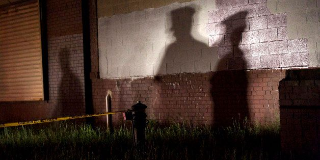 PHILADELPHIA, PA - MAY 13:  The shadow of a police officer is cast onto a building near the wreckage of an Amtrak passenger t