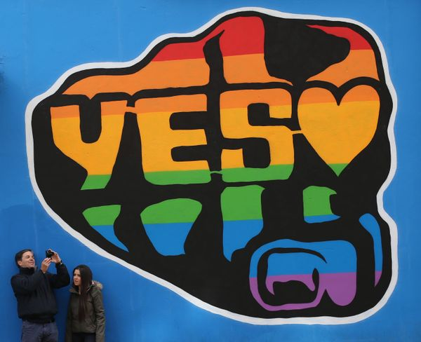 Members of the public beside a mural in Dublin's Temple Bar area by street artist SUMS supporting a yes vote in the forthcomi