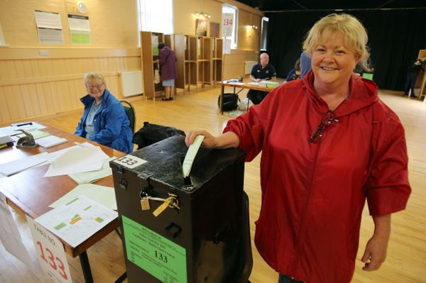 Mary Cassidy (R) drops her ballot paper in the ballot box at a polling station in Drumcondra, north Dublin on May 22, 2015. I
