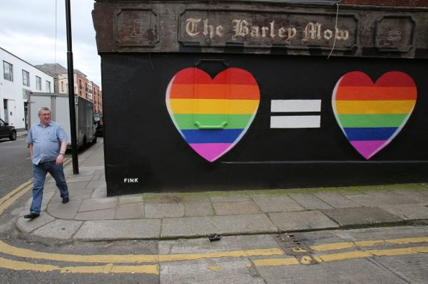 A man walks past a mural in favour of same-sex marriages in Dublin on May 21, 2015. Ireland goes to the polls tomorrow to vot