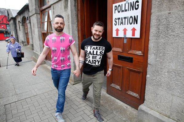 Partners Adrian, centre left and Shane, leave a polling station after casting their vote in Drogheda, Ireland, Friday, May 22