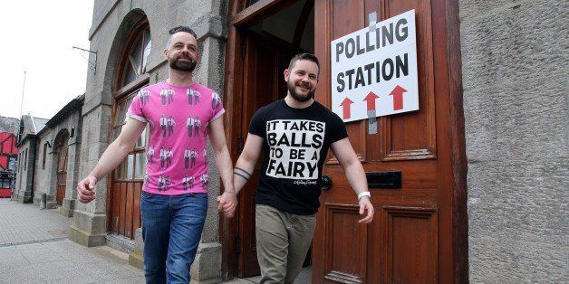 A gay couple pose holding hands as they walk out of a polling station after voting in Drogheda, north Dublin on May 22, 2015.