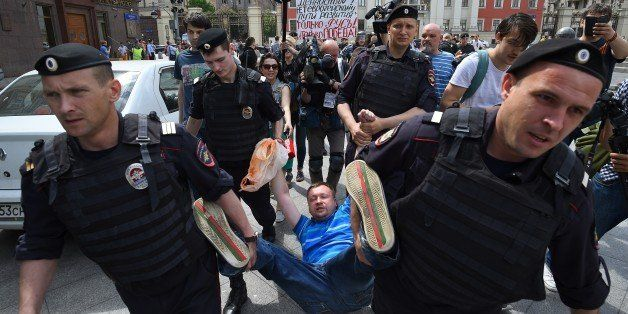Russian riot policemen detain gay and LGBT rights activist Nikolai Alexeyev (C) during an unauthorized gay rights activists r