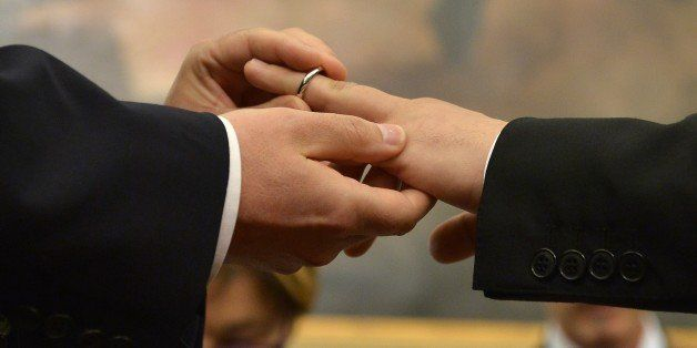 A same-sex couple exchanges rings after they registered their civil union at Rome's city hall on May 21, 2015 in Rome. The ci