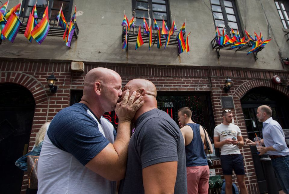 Doug Mest, left, and Mark Pelekakis, second left, of Los Angeles, kiss outside the Stonewall Inn after the U.S. Supreme court
