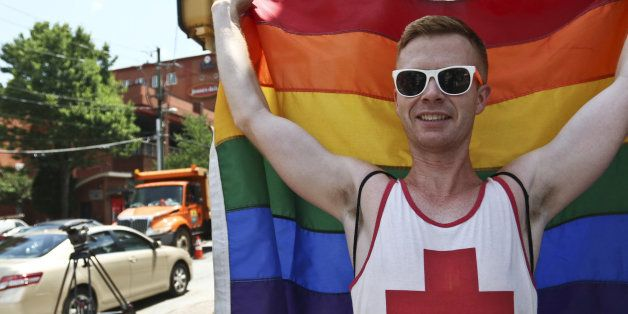 A man holds a flag celebrating the Supreme Court's decision legalizing gay marriage across the United States, on Friday, June