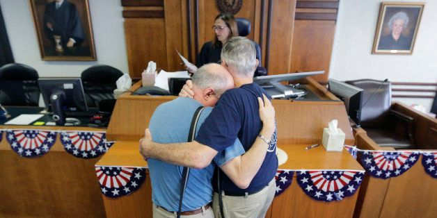 Gerald Gafford, right, comforts his partner of 28 years, Jeff Sralla, left, as they stand before Judge Amy Clark Meachum to r