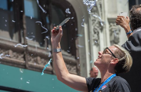 Abby Wambach takes a photo as she and her teammates from the U.S. Women's World Cup soccer team parade along Broadway to City