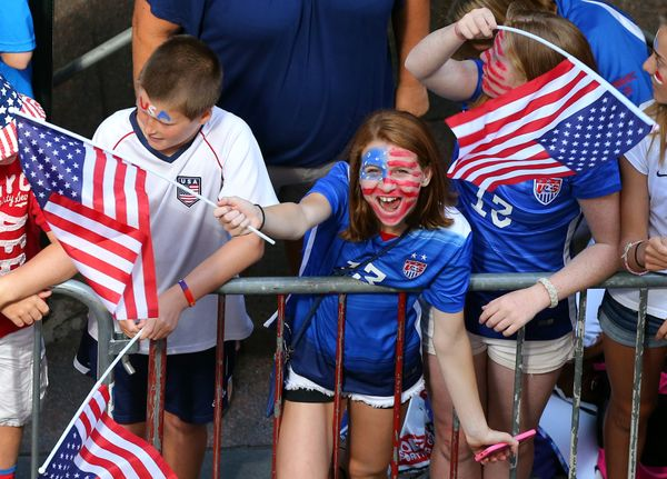 A young fan cheers while waiting for the ticker tape parade to celebrate the U.S. women's soccer team World Cup victory, Frid