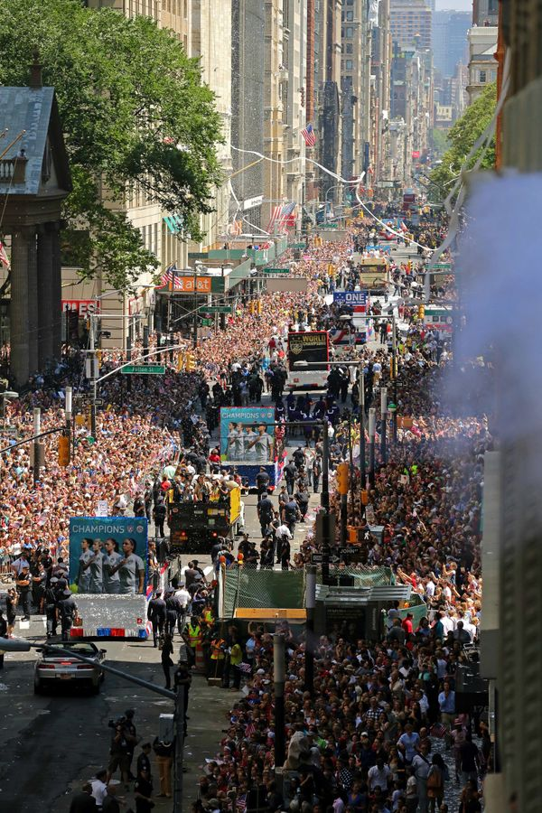 The U.S. Women's World Cup team stands on floats as they move through thousands of fans along Broadway, Friday, July 10, 2015