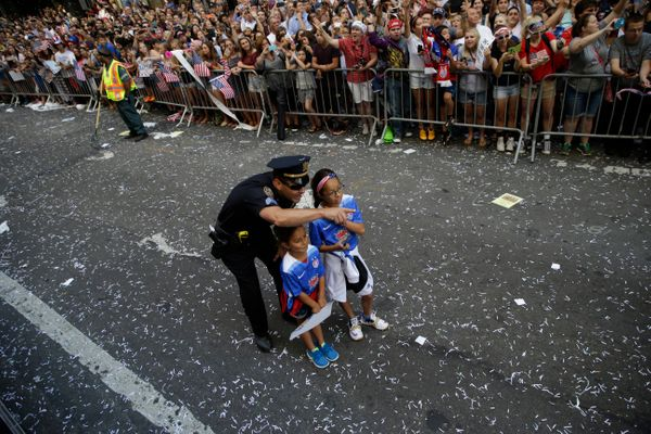 A police officer with two U.S. women's soccer team fans points as the floats with players makes its way up Broadway's Canyon