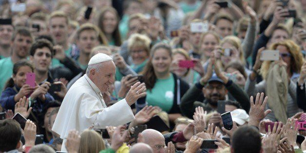 Pope Francis greets the crowd as he arrives for his weekly general audience at St Peter's square on September 30, 2015 at the
