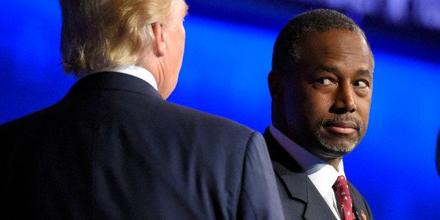 Ben Carson watches as Donald Trump takes the stage during the CNBC Republican presidential debate at the University of Colora