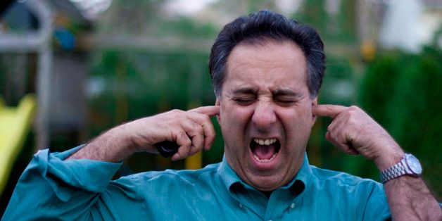 Man with fingers in his ears screaming.
