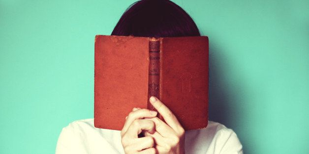 Woman's holding a book in front of her face.