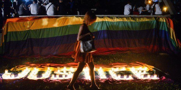 QUEZON CITY, PHILIPPINES - 2014/10/24: A transgender Filipino walks across the lit candles formed 'Justice' during a protest