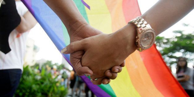 Filipino LGBTs (Lesbians Gays Bisexual and Transgenders) hold hands as they gather for a Gay Pride rally Saturday, June 27, 2