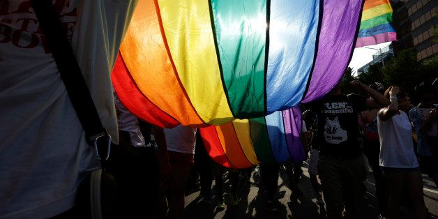 Participants march with a rainbow flag during the Korea Queer Festival in Seoul, South Korea, Sunday, June 28, 2015. Thousand