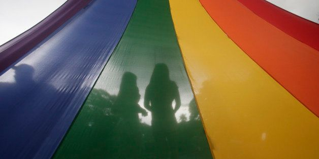 A LGBT (Lesbians Gays Bisexuals and Transgenders) couple is silhouetted by their rainbow-colored symbol while waiting to marc