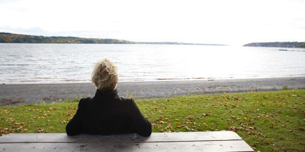 Mature woman sitting at picnic table overlooking river and autumn colors, rear view.