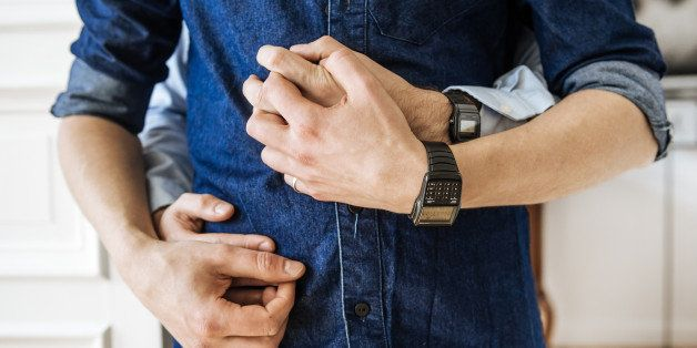 Close up shot of hands of a gay couple hugging. Focus on their hands in front of their body.