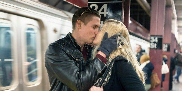 Romantic young couple kissing on New York City subway platform, New York, USA
