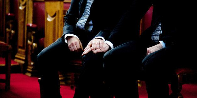 Civil gay marriage, 2 men holding hands while sitting on the chairs, wearing black suits. Background is brown and red, horizo