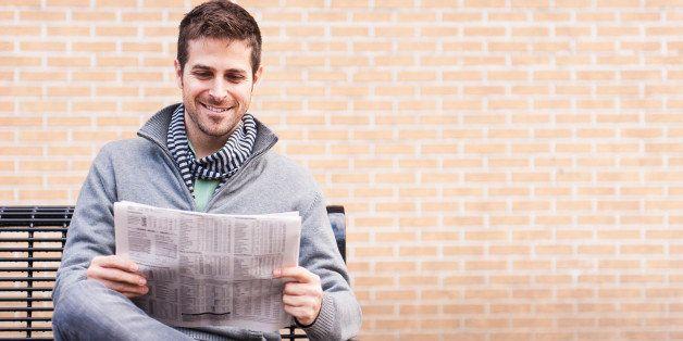 USA, New Jersey, Jersey City, Man on bench reading newspaper