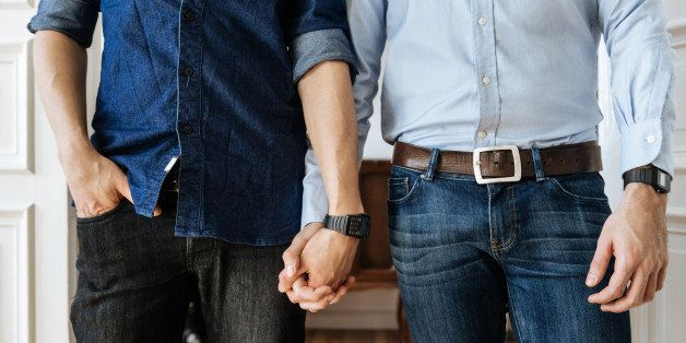Close up shot of a gay couple holding hands. Focus on their hands.