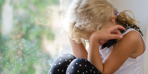 lonely blond girl sitting by the window with head in hands and crying