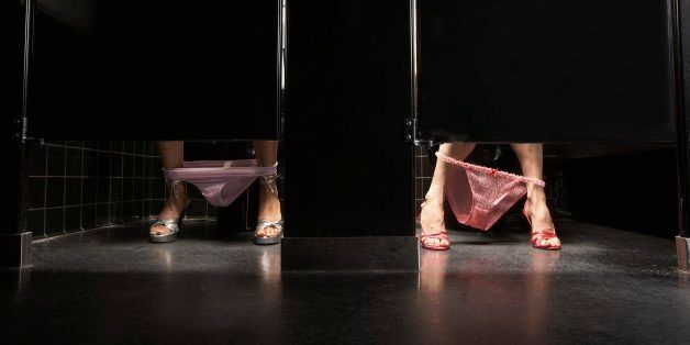 Women with underwear around ankles in restroom stalls