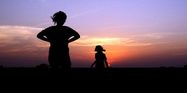 mother & daughter enjoying sunset.