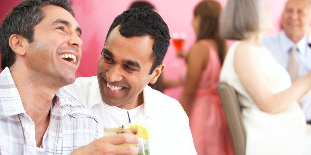 Two mature men having drinks and laughing in lounge