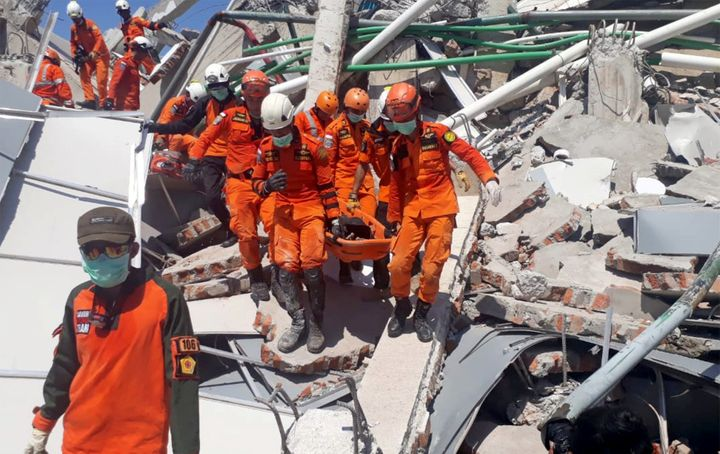 A search and rescue team evacuates a victim from the ruins of the Roa-Roa Hotel in Palu, Central Sulawesi, Indonesia on Septe