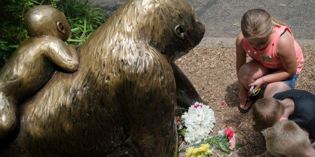 Children pause at the feet of a gorilla statue where flowers and a sympathy card have been placed, outside the Gorilla World