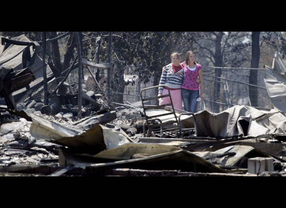 Sisters Laura, left, and Michelle Clements survey their fire-destroyed home, Tuesday, Sept. 6, 2011, in Bastrop, Texas. The C