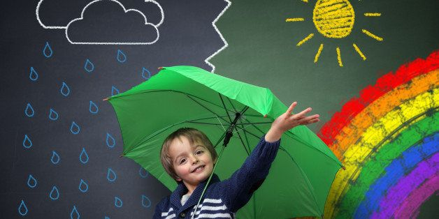 Child holding an umbrella standing in front of a chalk drawing of changing weather from rain storm to sun shine with a rainbo