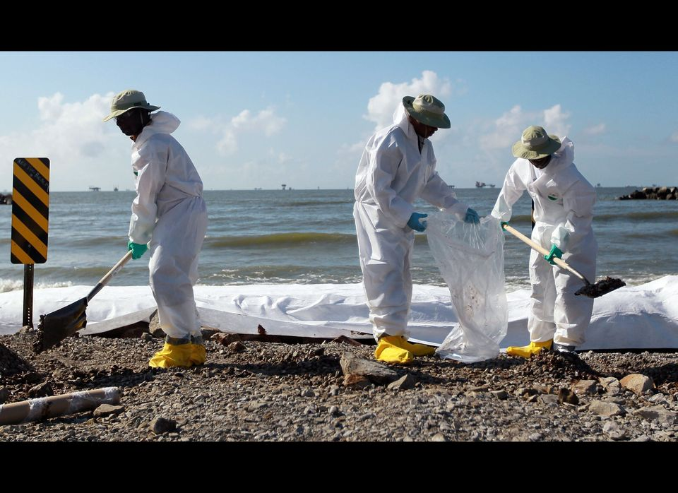 PORT FOURCHON, LA - JULY 03:  Workers clear off some of the oil washing on to Fourchon Beach from the Deepwater Horizon oil s