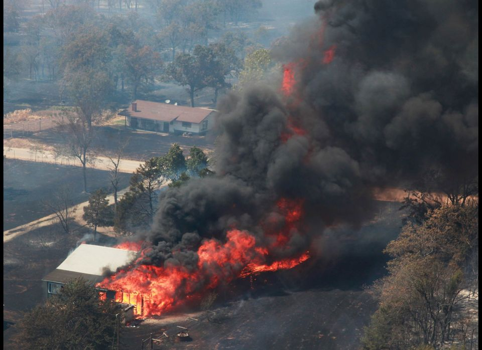 A house is engulfed in flames near Highway 48 and HW 38 junction east of Drumright, Okla., on Saturday, Aug 4, 2012. Emergenc