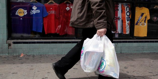 A man walks along the street with plastic bags in Los Angeles, Thursday, May 24, 2012. Now that the city of Los Angeles has t