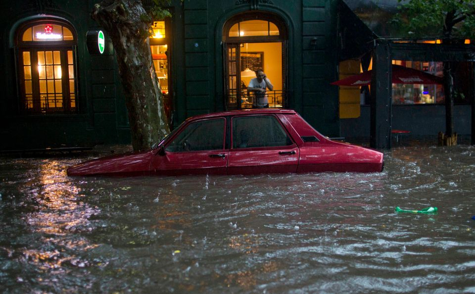 A car is submerged in flood water in front of a home in Buenos Aires, Argentina, Thursday, Dec. 6, 2012. Heavy rain flooded t