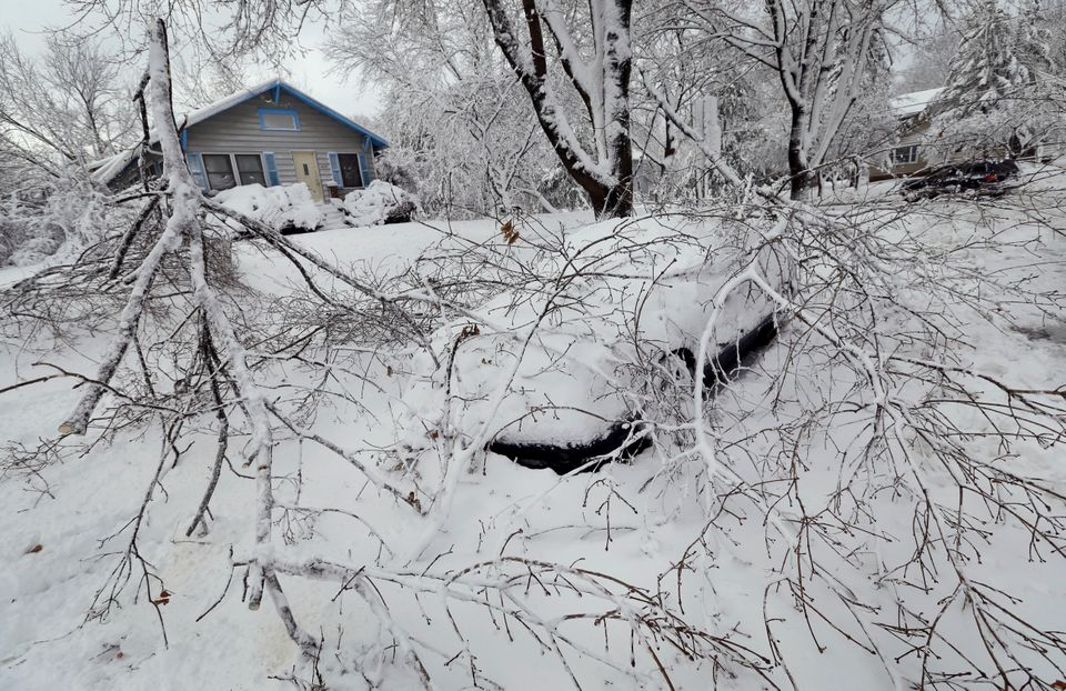 A car sits covered in snow and fallen tree branches, Thursday, Dec. 20, 2012, in Des Moines, Iowa. The first widespread snows