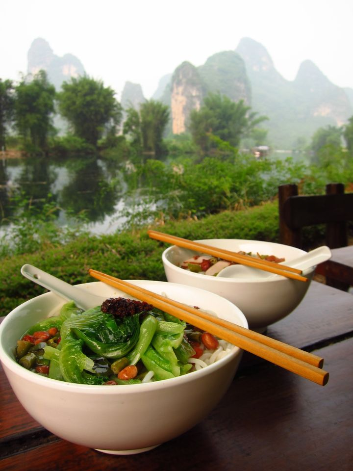 Bowl of round rice noodles with chopsticks and spoons on table in Yangshuo, China.