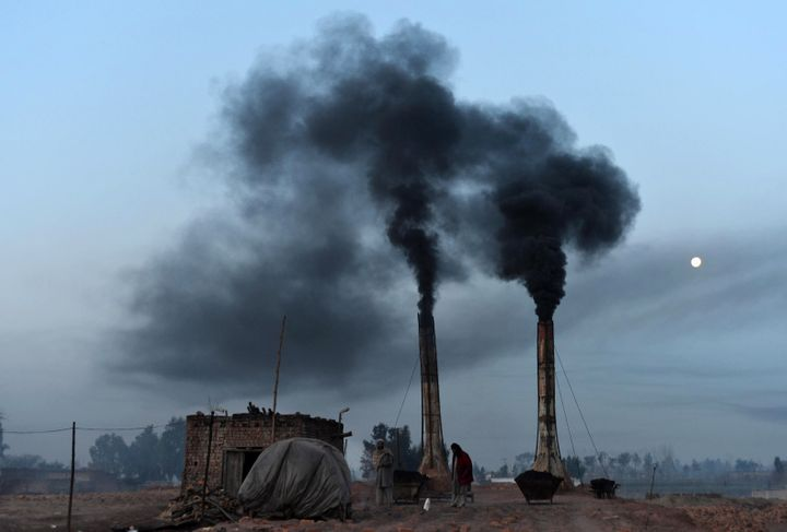 Labourers work as smoke rises from a brick kiln in Peshawar on January 30, 2013.  AFP PHOTO/A MAJEED        (Photo credit sho