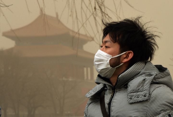 A Chinese man wears a facemask as Beijing is hit by a sandstorm as well as air quality worse than the highest classification