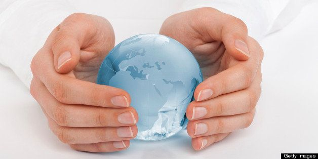 Hands of a woman protecting a globe.