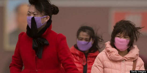 Chinese women cover their noses as Beijing is hit by a sandstorm as well as air quality worse than the highest classification