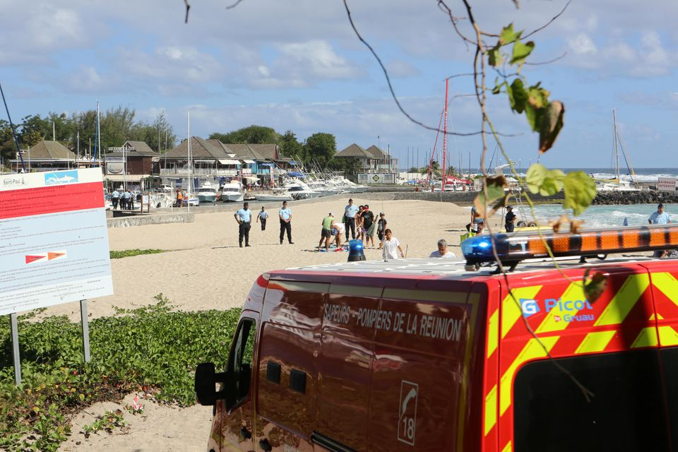 French gendarmes and tourists stand on the beach after a 36 year-old French surfer was attacked and killed by a shark on May