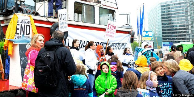 A few supporters of the conservationist body WWF, some of them standing on a boat, stage a protest against overfishing holdin