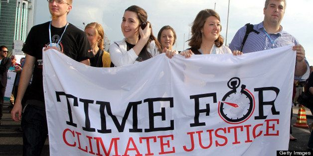 Activists carry placards during a rally in Doha on December 1, 2012 to demand urgent action addressing climate change as the
